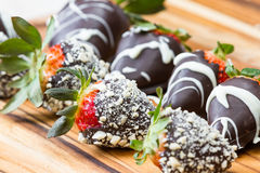 Chocolate dipped strawberries. Hand dipped strawberries in chocolates with some rolled in roasted cashews and some with a white chocolate drizzle Royalty Free Stock Images