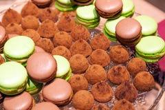 Chocolate do close up e bolinhos de amêndoa e trufas do pistache polvilhados com o cacau em uma placa de cristal Vista de acima T imagem de stock