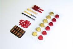 Chocolate doce da forma do coração envolvido na folha e nas medicinas imagem de stock