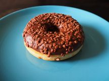 A chocolate donut on the blue plate in close view stock image