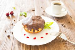 Chocolate donut or bun with an espresso on table Stock Image