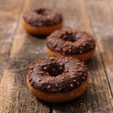 Chocolate donut. On wood background Stock Photos