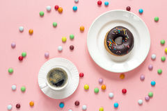 Chocolate donut with a cup of coffee on a pink background. Royalty Free Stock Images