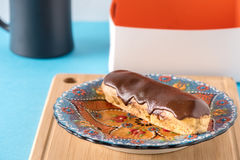 Chocolate donut ekler with coffee and blue background. Good Condition Stock Photo