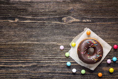 Chocolate donut with icing and colorful candy on a wooden table. Royalty Free Stock Photography