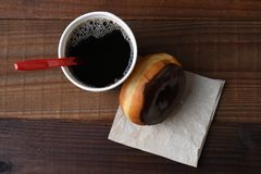 Chocolate donut leaning on a hot cup of coffee Royalty Free Stock Images