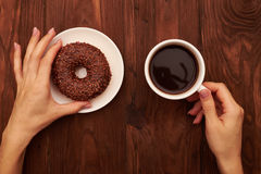 Chocolate donut and womans hand with coffee Stock Photo