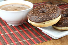 Chocolate donuts. On plate and bowl of hot chocolate Royalty Free Stock Photography