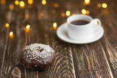 Chocolate donuts with coffee on a wooden table with beautiful lights stock photo