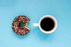 Chocolate donuts with cup of coffee on the blue background. Delicious donut Royalty Free Stock Photos