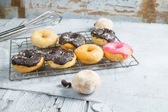 Chocolate donuts and pink donuts on the kitchen table stock images