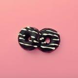 Chocolate donuts on pink vanilla background