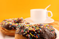 Chocolate donuts with sprinkles and coffee cup Royalty Free Stock Photography
