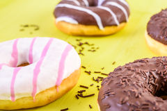 Chocolate Donuts On Yellow Background Stock Photos