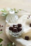 Chocolate dragee in a glass bowl on peachy cloth Stock Photography