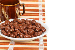 Chocolate dragees in a white saucer on a bamboo mat Royalty Free Stock Image