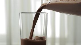Chocolate drink. Useful milkshake. Chocolate drink pouring into a glass stock video