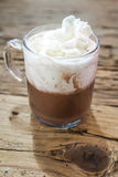 Chocolate drink with whipped cream in transparent cup on wooden Royalty Free Stock Image
