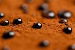Chocolate drops on cacao powder surface Royalty Free Stock Image