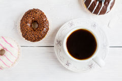 Chocolate e anéis de espuma vitrificados, rosa, branco, marrons na tabela e no copo de madeira brancos do café preto, vista super Imagens de Stock Royalty Free