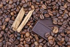Chocolate e canela no fundo dos feijões de café Fotografia de Stock Royalty Free