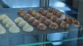Chocolate e doces de chocolate brancos na janela da loja vídeos de arquivo