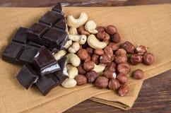 Chocolate e porcas com o guardanapo na madeira Imagens de Stock