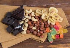 Chocolate e porcas com o guardanapo na madeira Imagens de Stock Royalty Free