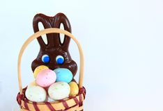 Chocolate Easter Bunny. Behind a pot of candied eggs Stock Photos