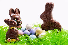 Chocolate Easter bunny,candy,eggs. Three chocolate Easter bunnies  on grass with colored egg candy isolated on white background Stock Photos