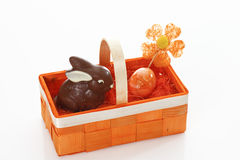 Chocolate easter bunny and egg in orange basket Royalty Free Stock Photos