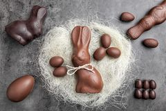 Chocolate Easter bunny and eggs in a nest on rustic background royalty free stock photos