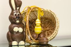 Chocolate Easter bunny eggs and sweets in Easter basket. Royalty Free Stock Image