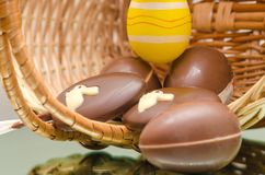 Chocolate Easter bunny eggs and sweets in Easter basket. Stock Image