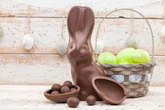 Chocolate Easter bunny, eggs and sweets on rustic background royalty free stock photography