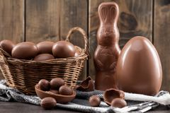 Chocolate Easter bunny, eggs and sweets on rustic background stock photography