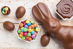 Chocolate Easter bunny, eggs and sweets on rustic background royalty free stock images