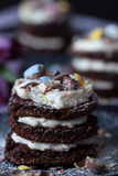 Chocolate Easter Cakes with Frosting and Purple Tulips Royalty Free Stock Images