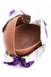 Chocolate easter egg. A halved milk chocolate Easter egg in foil wrapping Royalty Free Stock Images