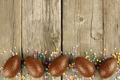 Chocolate Easter egg border on wood. Chocolate Easter egg bottom border over a wood background Stock Photo