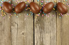 Chocolate Easter egg border on wood Royalty Free Stock Photo