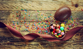 Chocolate Easter egg with candy on table Stock Photos