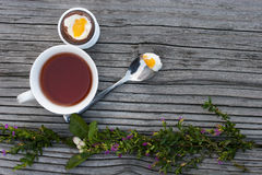 Chocolate Easter egg and cup of tea. Chocolate Easter egg next to spoon with yolk and cup of tea on the wood background with flowers. Landscape orientation Stock Photo