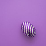 Chocolate easter egg with purple foil wrapper. Easter eggs with stripes, on a plain purple background Stock Images