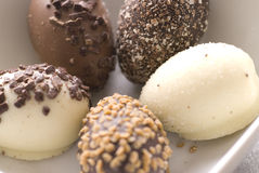 Chocolate easter eggs. A close up view of five different easter eggs made of dark or white chocolate with various types of nut and sprinkle toppings stock images