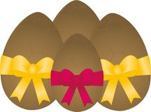 Chocolate Easter Eggs. Scrumptious chocolate easter eggs tied up with beautiful gold and red bows Stock Images