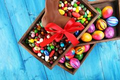 Chocolate Easter eggs and chocolate bunny and colorful sweets. stock photos