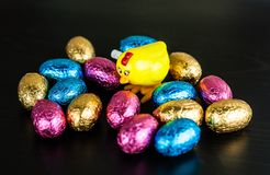 Chocolate Easter eggs with chicken toy. Chocolate Easter eggs in colorful foil on dark background with small windup chicken toy stock image