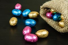 Chocolate Easter eggs in colorful foil. On dark background scattered from small jute bag stock photos