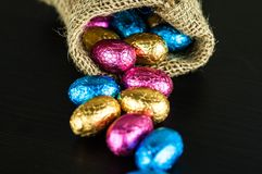 Chocolate Easter eggs in colorful foil scattered from jute bag. Chocolate Easter eggs in colorful foil on dark background scattered from small jute bag stock image